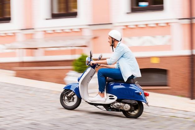 Genieten van zijn scooterrit. zijaanzicht van jonge man in helm rijden scooter langs de straat