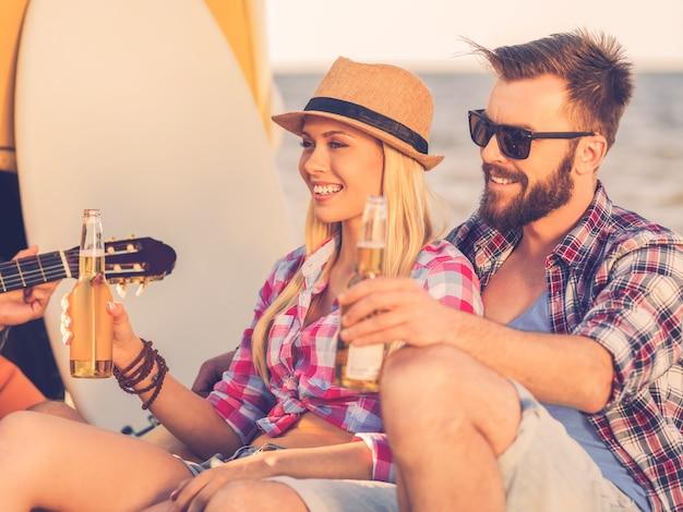 Genieten van zomerdag. gelukkig jong stel dat flessen bier vasthoudt terwijl ze aan de kust zitten met minibus en skimboard op de achtergrond
