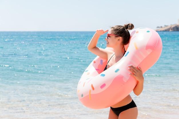 Genieten van zonnebrand en vakantie. portret van een gelukkig meisje dat door een opblaasbare ring kijkt