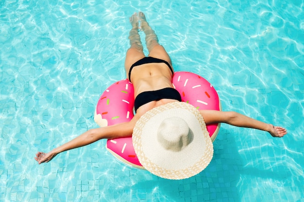 Genieten van zonnebrandvrouw in bikini op de opblaasbare matras