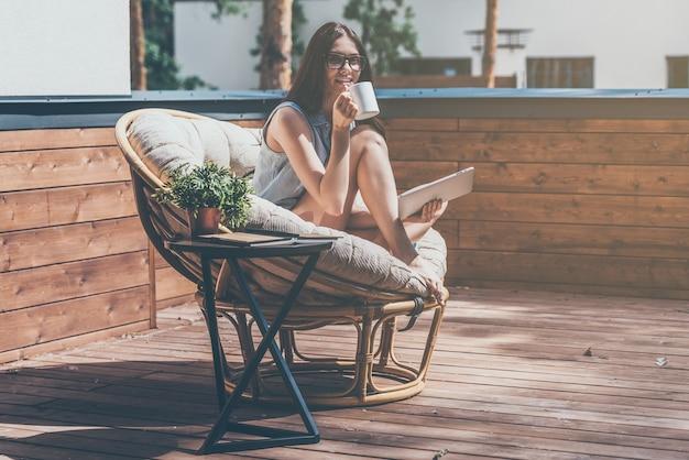 Genietend van haar ochtendkoffie. mooie jonge glimlachende vrouw die een koffiekopje vasthoudt en naar de camera kijkt terwijl ze in een grote comfortabele stoel op haar buitenterras zit