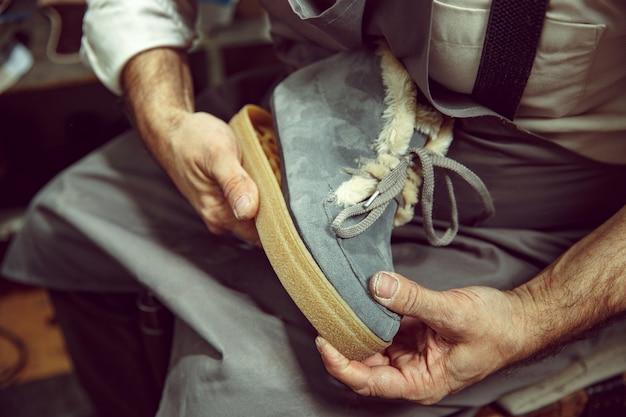 Genietend van het proces van het maken van op maat gemaakte schoenen. werkplek van schoenontwerper. handen van schoenmaker omgaan met schoenmaker tool, close-up