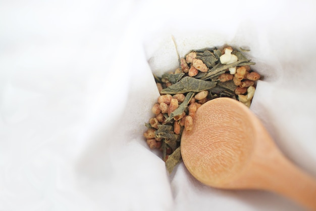 Genmaicha, een japanse bruine rijst groene thee bestaande uit gedroogde groene thee vermengd met geroosterde gepofte bruine rijst met een houten lepel op witte stof achtergrond