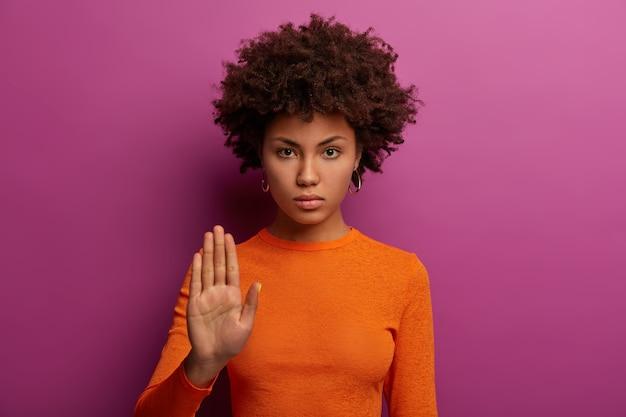 Genoeg alsjeblieft. ernstige strenge vrouw maakt stopgebaar, toont verbod en vraagt wacht even, wijst iets af, draagt oranje trui, geïsoleerd op paarse muur. nee betekent nooit, niet erin