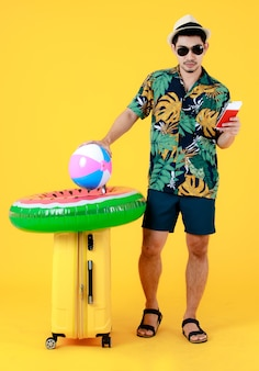 Genoten van een jonge aziatische man in een kleurrijk hawaïaans shirt houdt een paspoort in de buurt van een koffer. full body studio portret op gele achtergrond. gelukkig zomervakantie reizen concept.