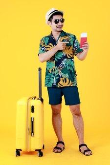 Genoten van een jonge aziatische man in een kleurrijk hawaïaans shirt houdt vast en wijst met de vinger naar het paspoort in de buurt van de koffer. full body studio portret op gele achtergrond. gelukkig zomervakantie reizen concept.