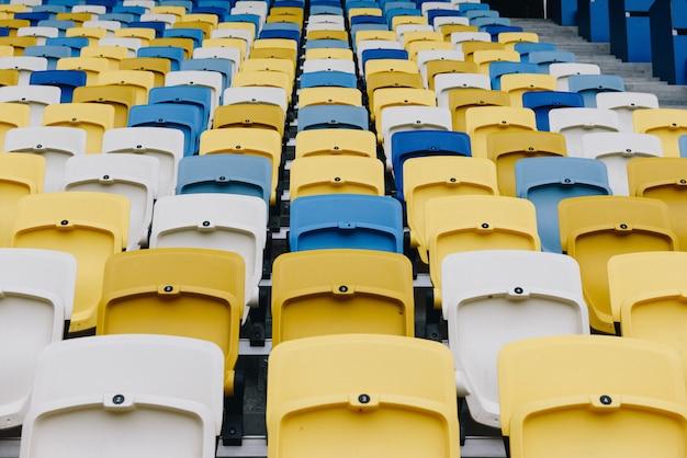 Genummerde rijen gele en blauwe stoelen in een voetbalstadion
