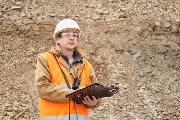 Geoloog of mijningenieur met zaktablet voor werkdocumentatie buiten op de mijnsite