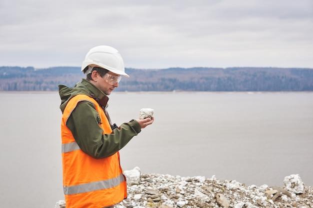 Geoloog of mijningenieur onderzoekt een monster van een mineraal uit een talus op een rivieroever