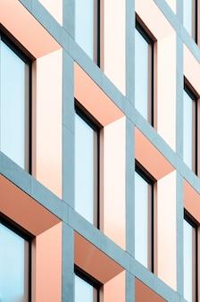 Geometrisch deel van de gevel van het gebouw. moderne architectuur van commercieel gebouw muren en ramen gemaakt van glas.