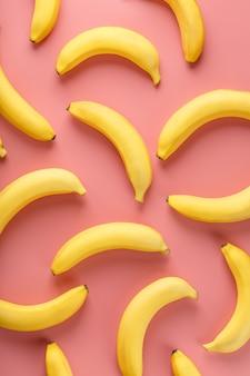 Geometrisch patroon van bananen op een roze achtergrond. het uitzicht vanaf de top. minimale vlakke stijl. pop-artontwerp, creatief zomerconcept.