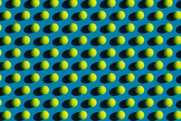 Geometrisch patroon van tennisballen met sterke schaduwen op blauw