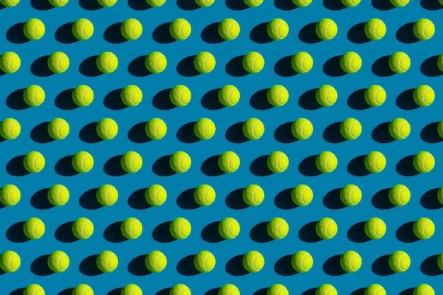 Geometrisch patroon van tennisballen met sterke schaduwen op een blauw