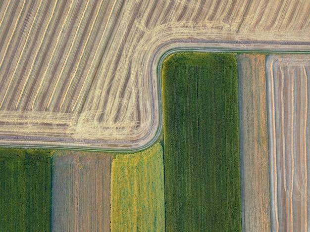 Geometrische abstracte achtergrond van landbouwvelden met verschillende gewassen en na de oogst, gescheiden door de weg. een vogelperspectief vanaf de drone.