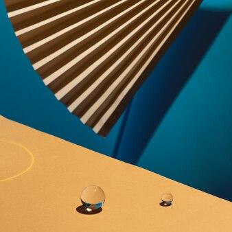 Geometrische compositie met kleurrijke papier, ventilator en glazen bol