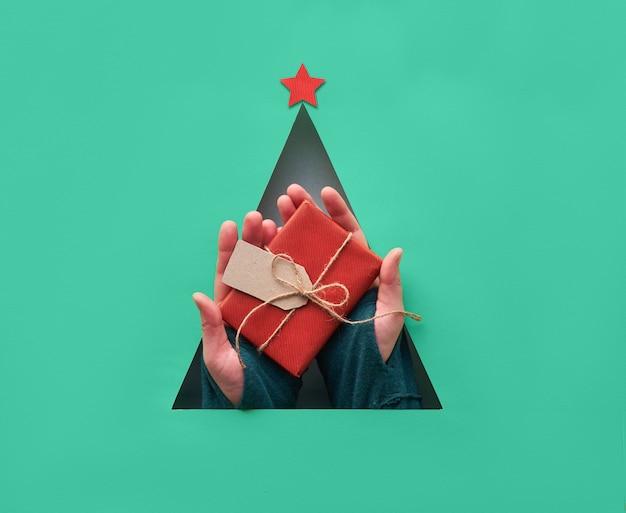 Geometrische creatieve kerst plat lag in biscay groene en rode kleuren. kerstballen in driehoekig papier gat in een driehoekige vorm van kerstboom met rode papieren ster.