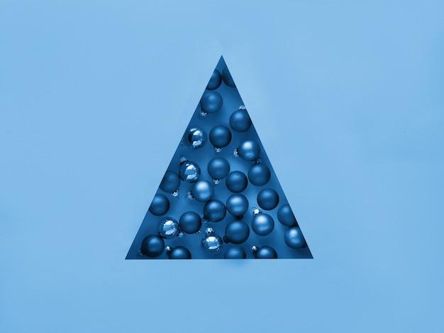 Geometrische creatieve kerst plat lag. zwart-wit afbeelding afgezwakt in klassieke blauwe kleur, trendy kleur 2020. kerstballen in driehoekig papier gat in driehoekige vorm van kerstboom.