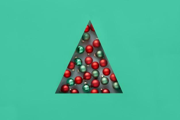 Geometrische creatieve kerstflat lag in biscay groene en rode kleuren met kerstversiering in driehoekig papier gat in een vorm van kerstboom.