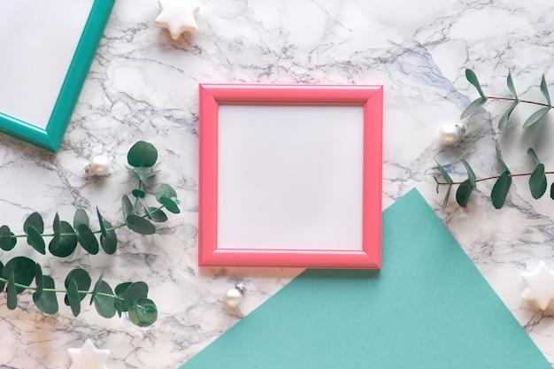 Geometrische kerst plat lag met roze en groene kaders en groen papier. verse eucalyptustakjes en witte snuisterijen met zwarte sterren. tekstruimte, kopie-ruimte. plat lag marmeren achtergrond.