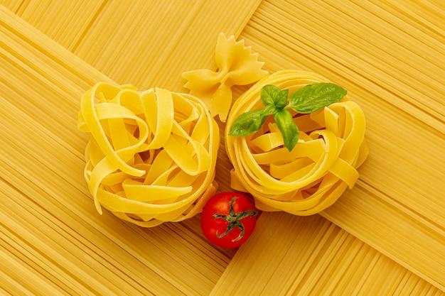 Geometrische opstelling van rauwe spaghetti met tagliatelle en tomaat