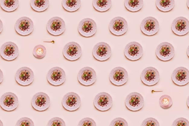 Geometrische patroon met pannenkoeken op roze plaat en kopje koffie op roze achtergrond.