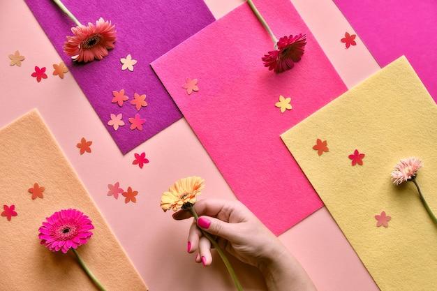 Geometrische tweekleurige plat lag op papier en voelde geometrische gelaagde achtergrond. gerbera bloeit in de hand en bloemenconfettien.