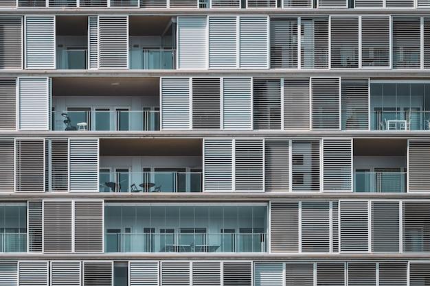 Geometrische vooraanzicht van de luiken en balkons van een stedelijk gebouw gerangschikt in doorlopende rijen