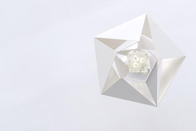 Geometrische witte moderne metalen kroonluchter hangend aan het witte plafond, onderaanzicht.