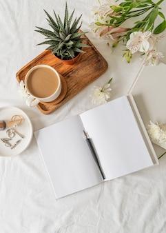 Geopend blanco notitieboekje met koffie, een plant en bloemen op een houten dienblad