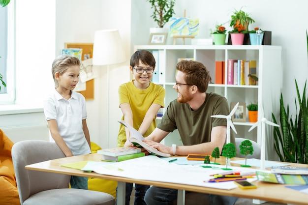 Geopend boek dragen. verlegen kleine jongens die zijn bebaarde leraar vragen stellen over ecologie terwijl ze educatieve lessen hebben
