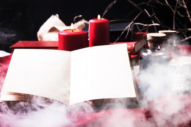 Geopend boek in rook met halloween-attributen