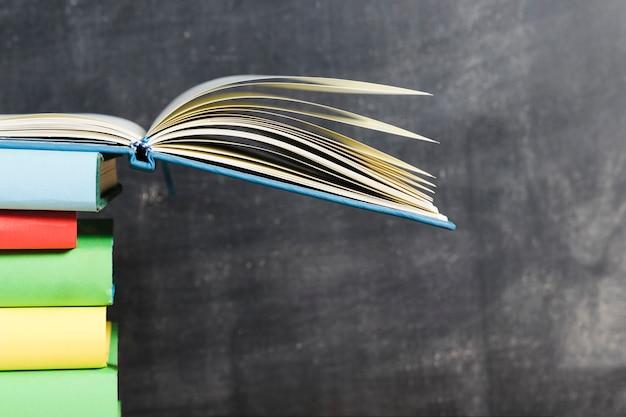 Geopend boek op levendige stapel tegen schoolbord