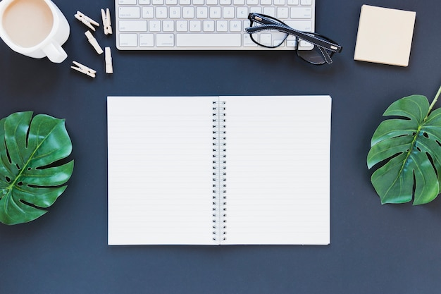Geopend notitieboekje dichtbij toetsenbord en koffiekop op bureau met bladeren en glazen