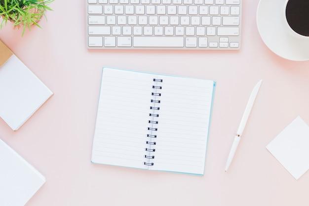 Geopend notitieboekje dichtbij toetsenbord en koffiekop op roze bureau