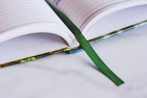 Geopend notitieboekje met groene lintreferentie op witte marmeren achtergrond