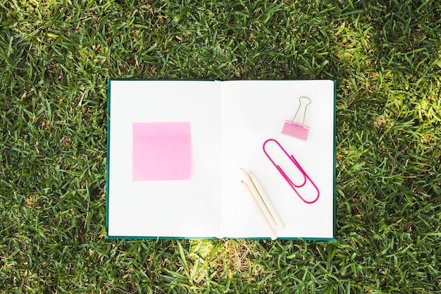 Geopend notitieboekje met roze kantoorbehoeften