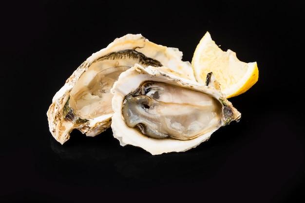 Geopend oesters, ijs en citroen op een zwarte ondergrond