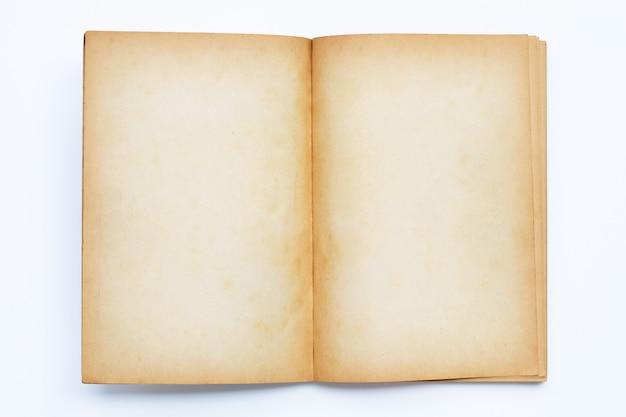 Geopend oud boek dat op wit wordt geïsoleerd
