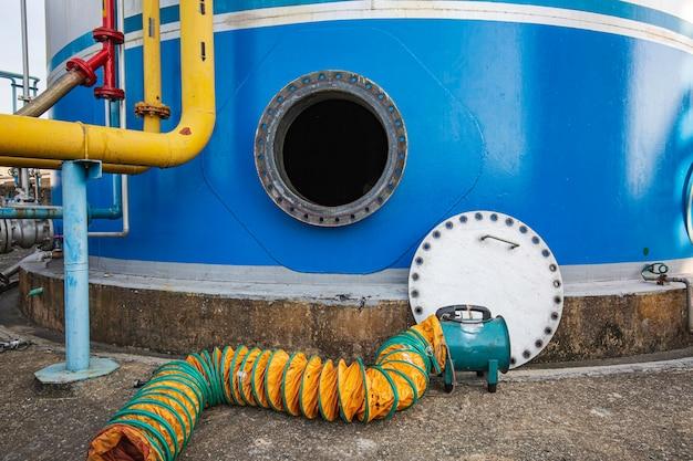 Geopend roestig mangat op de blauwe brandstoftank en frisse lucht van de ventilator in de beperkte ruimte van de olieopslagtank;