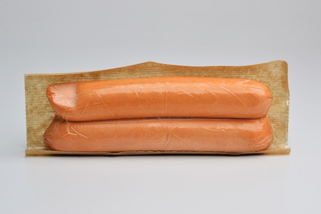 Geopend transparant plastic dienblad van verse ruwe geïsoleerde worsten