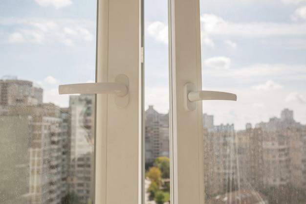 Geopend wit plastic vinylvenster met de achtergrond van flatgebouwen met meerdere verdiepingen