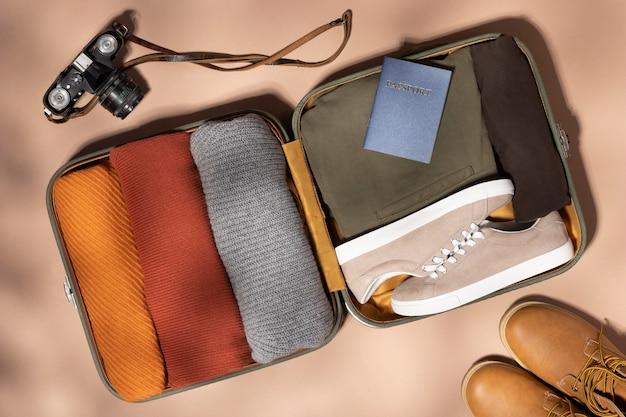 Geopende bagage met gevouwen kleding en camera