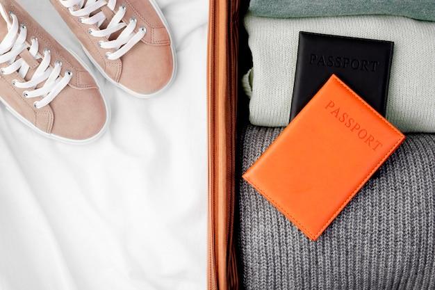 Geopende bagage met opgevouwen kleding en paspoort