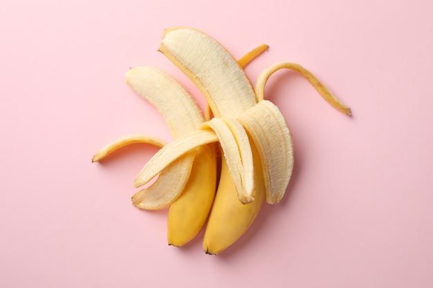 Geopende bananen op roze tafel. vers fruit