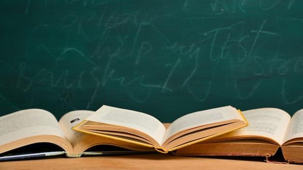 Geopende boeken op houten tafel over groen schoolbord. terug naar schoolconcept