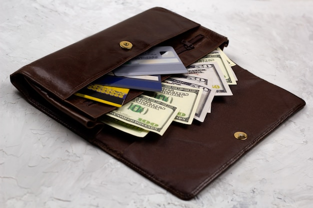 Geopende bruine lederen portefeuille vol dollars en creditcards