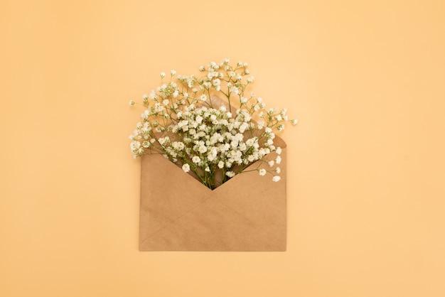 Geopende envelop met bloemenregelingen op roze achtergrond, hoogste mening. feestelijk begroetingsconcept