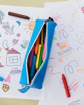 Geopende etui met waskrijtjes geplaatst op tekeningen van kinderen
