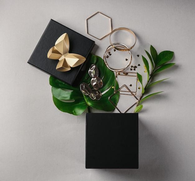 Geopende geschenkdoos en gouden accessoires op lichte achtergrond, bovenaanzicht