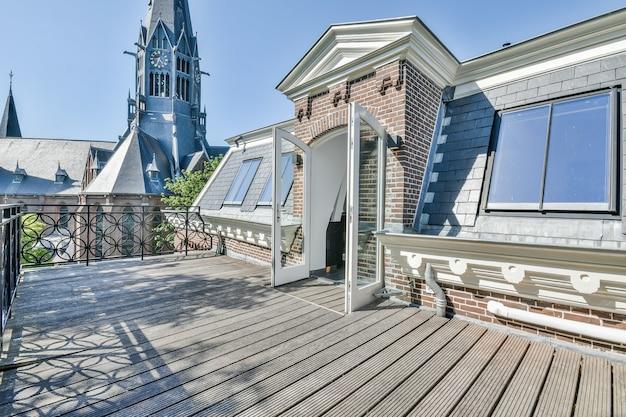 Geopende glazen deur van huisje die leidt naar terras op dak met houten vloer op zonnige dag